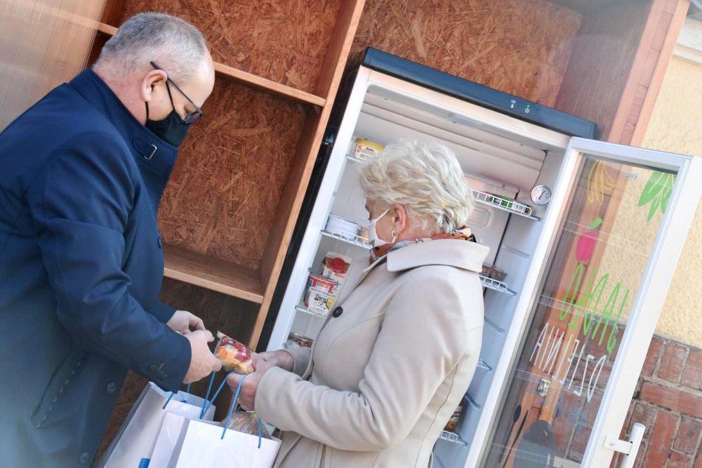 jadłodzielnia starosta Leszek Bizoń i członkini zarządu Krystyna Kuczera uzupełniają lodówkę społeczną w artykuły spożywcze